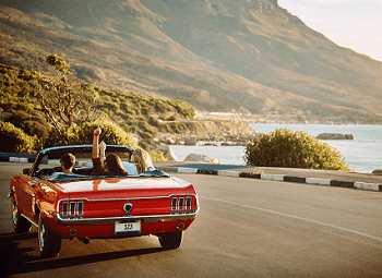 Three people in an older red convertible driving down the freeway on the coast